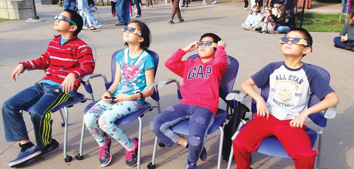 children watching eclipse with safety glasses at library